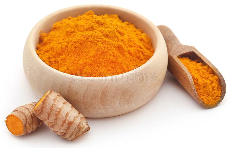 Raw turmeric with powder. In a wooden bowl royalty free stock image