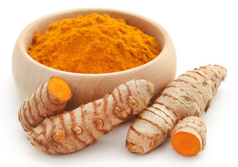 Raw turmeric with powder. In a wooden bowl stock photos