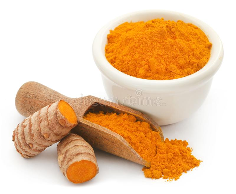 Raw turmeric with powder. In small bowl over white background stock photo