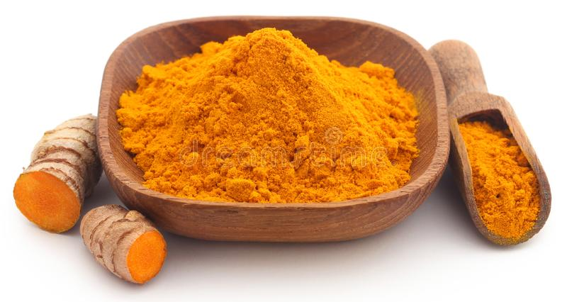 Raw turmeric with powder. In small bowl over white background stock photography