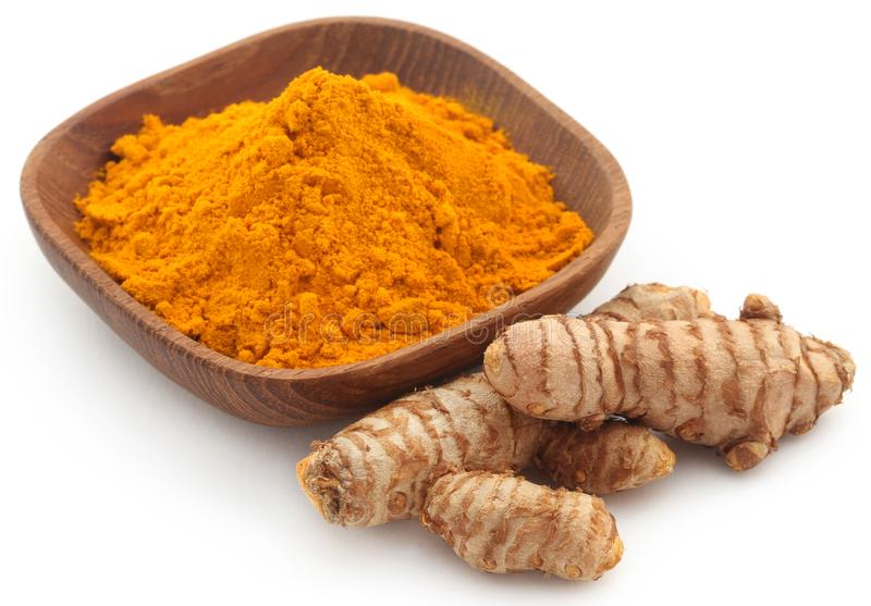Raw turmeric with powder. In small bowl over white background royalty free stock photography