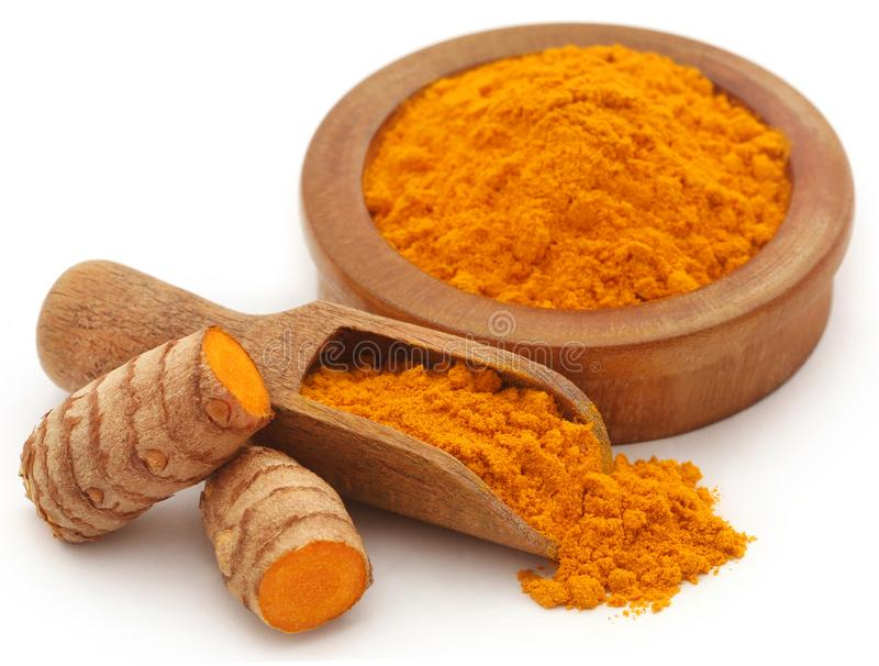 Raw turmeric with powder. In wooden scoop and  bowl over white background royalty free stock photography