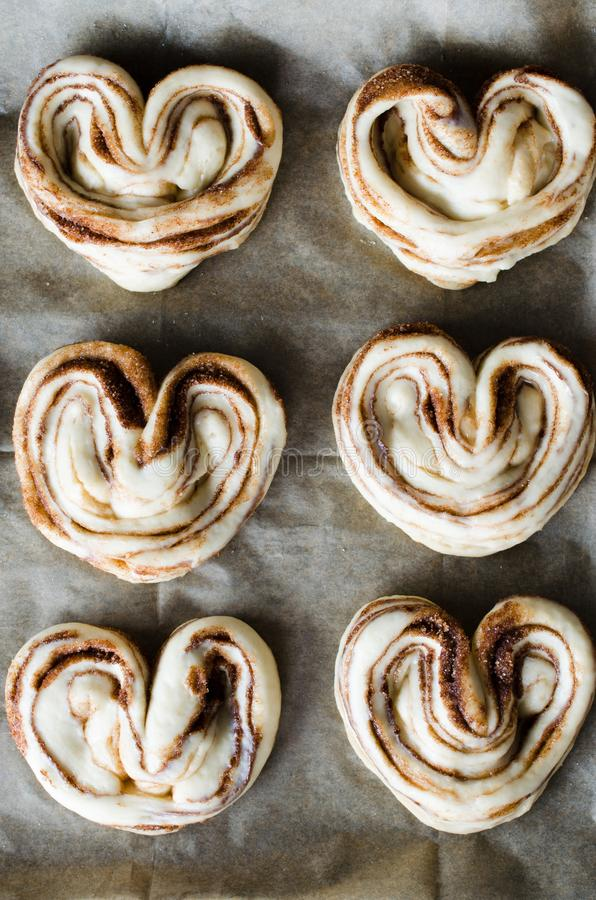 Raw unbaked buns. Yeast dough buns with sugar and cinnamon on baking paper, close-up stock photos