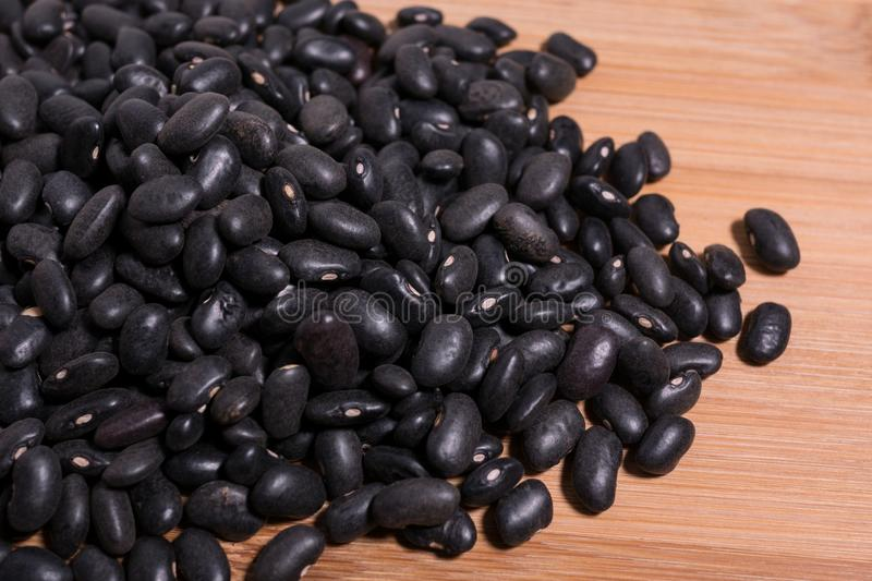 Raw uncooked black beans close up detail on natural wood background royalty free stock photo