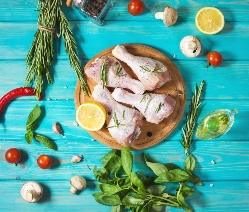 Raw uncooked chicken legs, drumsticks on blue wood background, meat with ingredients for cooking. royalty free stock images