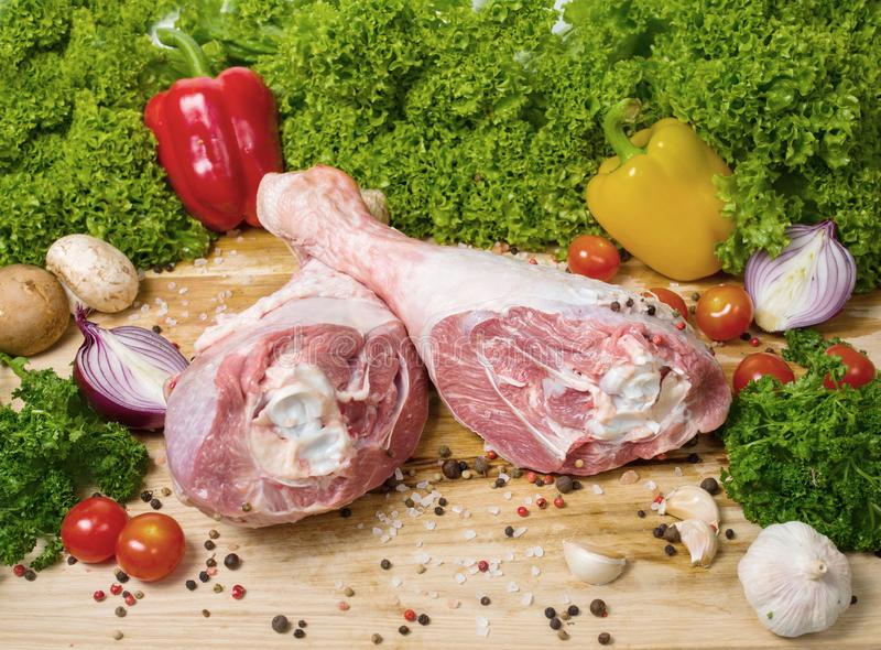 Raw uncooked chicken legs, drumsticks on a wooden board, meat with ingredients for cooking. Close-up photo royalty free stock image