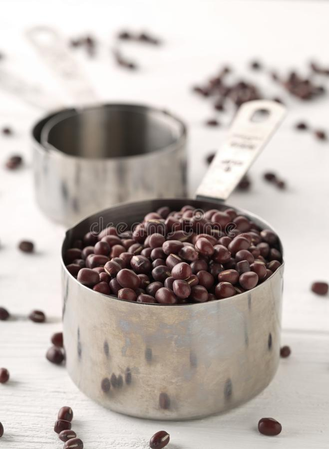 Raw, uncooked, dried adzuki red mung beans in metal measurement cups on white wooden table background stock photo