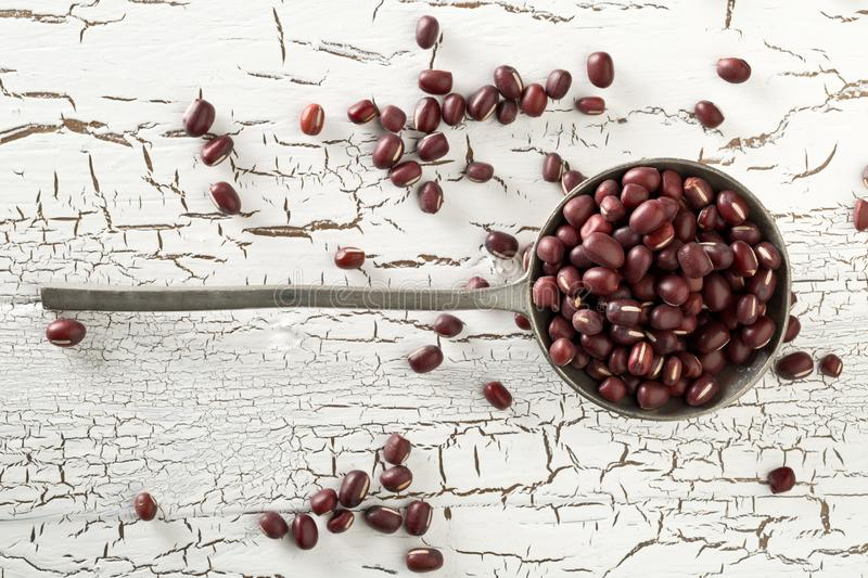 Raw, uncooked, dried adzuki red mung beans in metal spoon on white rustic wood table background top view flat lay stock photo