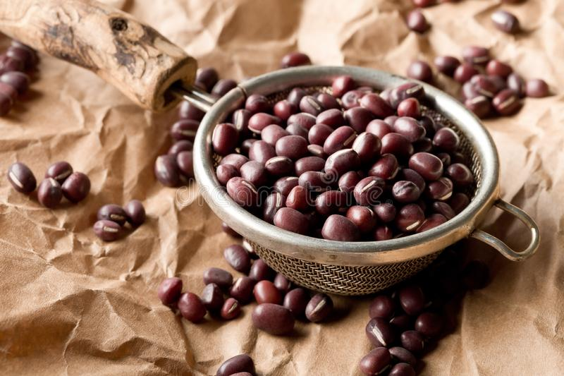 Raw, uncooked, dried adzuki red mung beans in small sieve on brown packing paper background royalty free stock photos