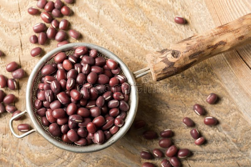 Raw, uncooked, dried adzuki red mung beans in small sieve on rustic wood table background with selective focus top view flat lay royalty free stock images