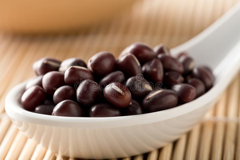 Raw, uncooked, dried adzuki red mung beans in white spoon on bamboo mat background stock photography