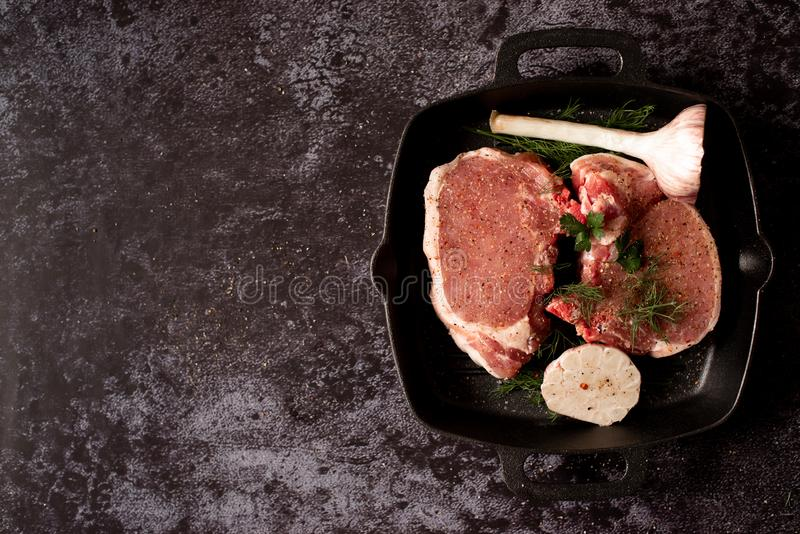 Raw uncooked lamb meat chops with rosemary and garlic in black iron grilling pan, top view, horizontal composition.  stock photo