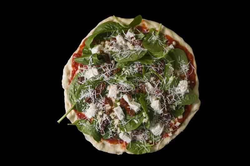 Raw uncooked pizza with spinache dried tomatoes and feta cheese stock photography