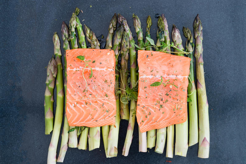 Raw uncooked salmon and asparagus on baking tray royalty free stock image