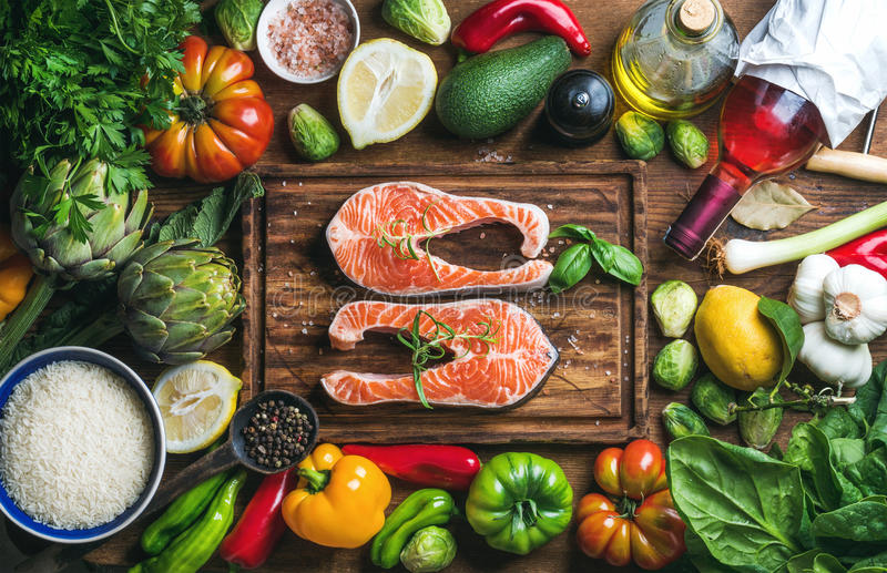Raw uncooked salmon fish with vegetables, rice, herbs, spices and wine on chopping board over rustic wooden background royalty free stock images