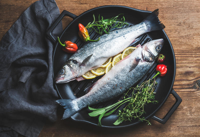 Raw uncooked seabass fish with lemon slices, herbs and spices on black grilling iron pan over rustic wooden background. Top view stock photography