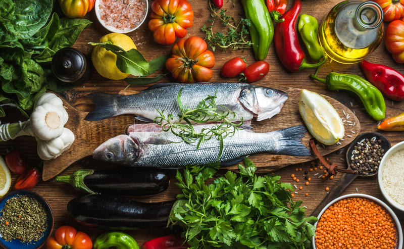 Raw uncooked seabass fish with vegetables, grains, herbs and spices on chopping board over rustic wooden background. Top view royalty free stock image