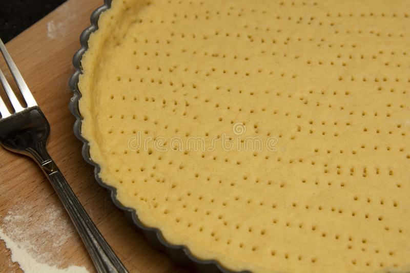 Raw, uncooked tart pie preparation, dough. Cooking apple, fruit pie. Cookign process. Kitchen table stock photos