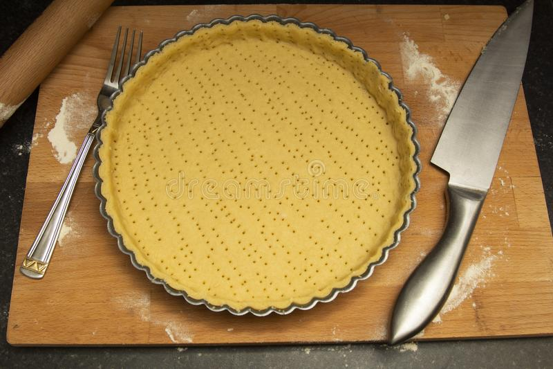 Raw, uncooked tart pie preparation, dough. Cooking apple, fruit pie. Cookign process. Kitchen table stock images