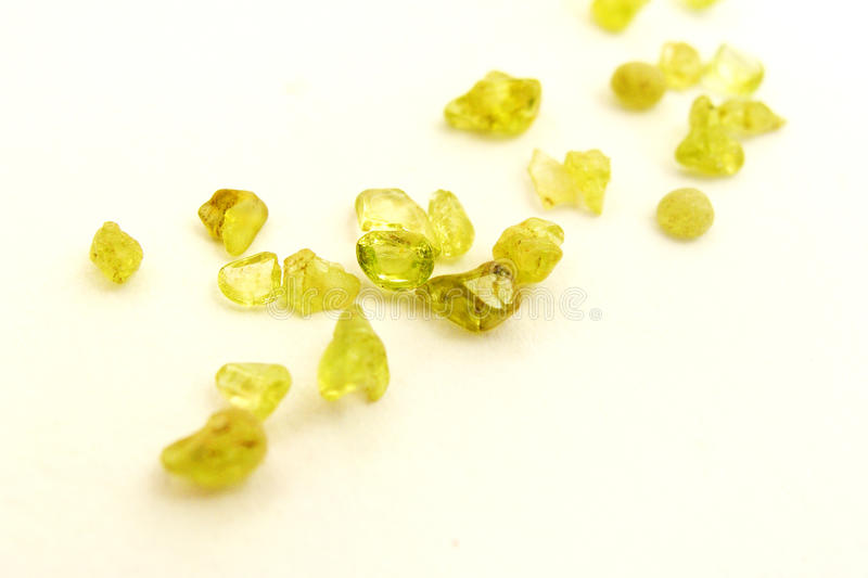 Raw uncut Peridot gem stones, white background. An image showing a geological sample of raw peridot rocks in olive green color. Hobby image for rock collecting royalty free stock images