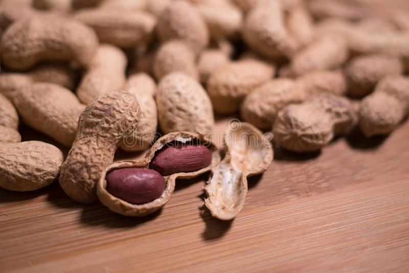 Raw unshelled peanuts close up on natural wooden background shallow depth of field stock image