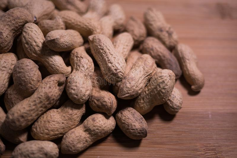 Raw unshelled peanuts close up on natural wooden table background. royalty free stock photography