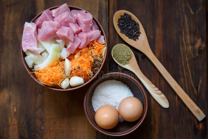 Raw veal cut into pieces with vegetables and other ingredients ready to cook on wooden rustic table. royalty free stock images