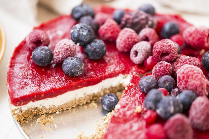 Raw vegan berries tart cake with biscuits, cashew nuts cream cheese, raspberries and blueberries jelly topping, healthy fresh stock photography