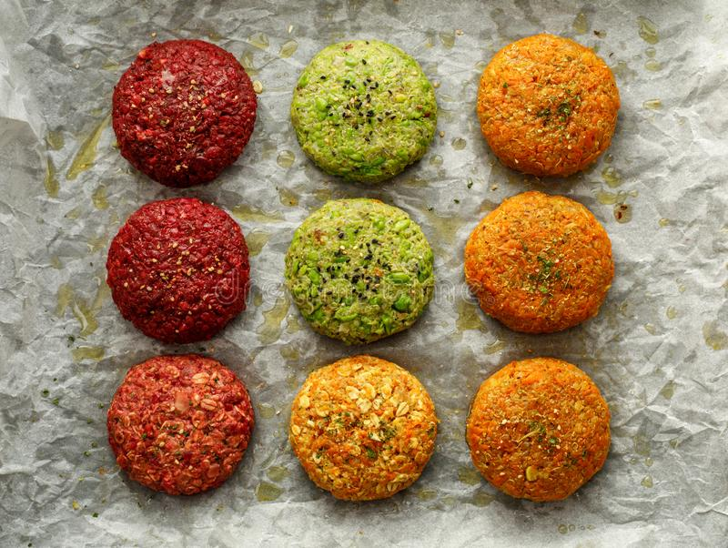 Raw vegan burgers made of beetroot, green peas, carrots, groats and herbs on white parchment prepared for baking, top view. stock photos