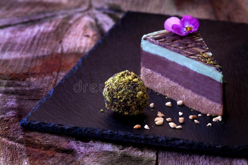 Raw Vegan Cake. Delicious slice of a raw vegan cake with a comestible flower royalty free stock images