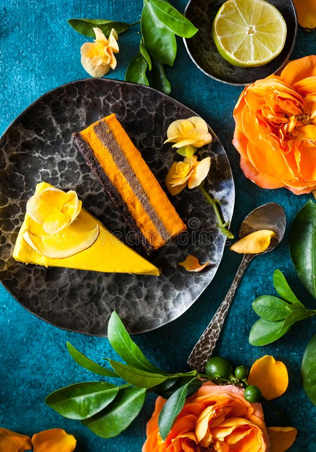 Raw vegan cakes with flowers on blue background. Raw vegan sweet cakes with mango,pineapple, buckthorn and nuts stock images