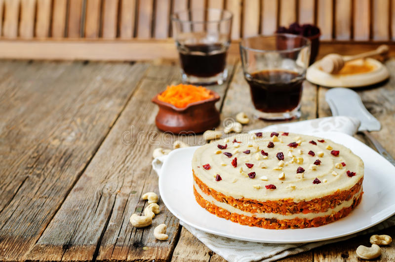 Raw vegan carrot cake with cashew cream and dried cranberries royalty free stock photography