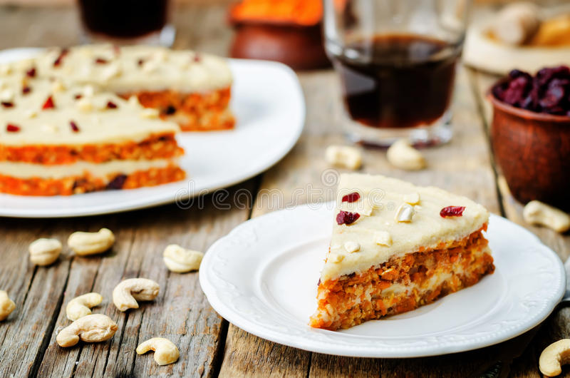 Raw vegan carrot cake with cashew cream and dried cranberries royalty free stock images
