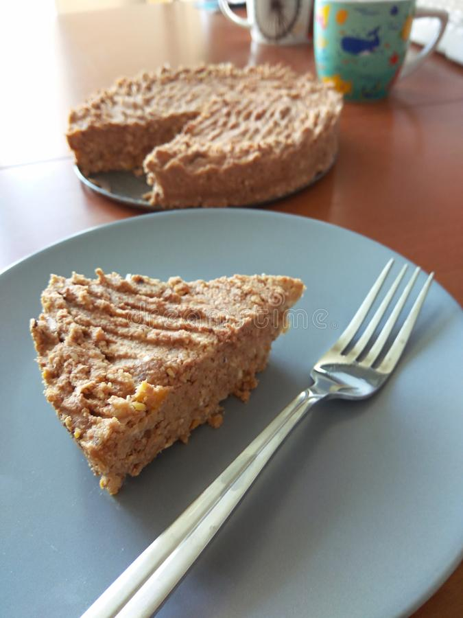 Raw vegan chickpeas blondies cake on blue plate. Close up vegetarian dessert coconut carrot protein diet. Sugar free stock image