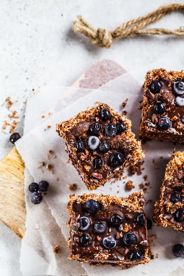 Raw vegan coconut chocolate dessert with blueberries, top view . Healthy vegan food concept. Raw vegan coconut dessert with blueberries on the board. Healthy royalty free stock photo