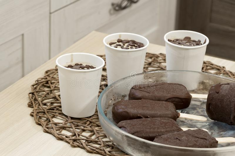 Raw vegan diet ice cream. Delicious homemade dessert with natural chocolate. Popsicles on a sticks and portions in paper. Cups. Glass plate on wicker tablecloth royalty free stock image