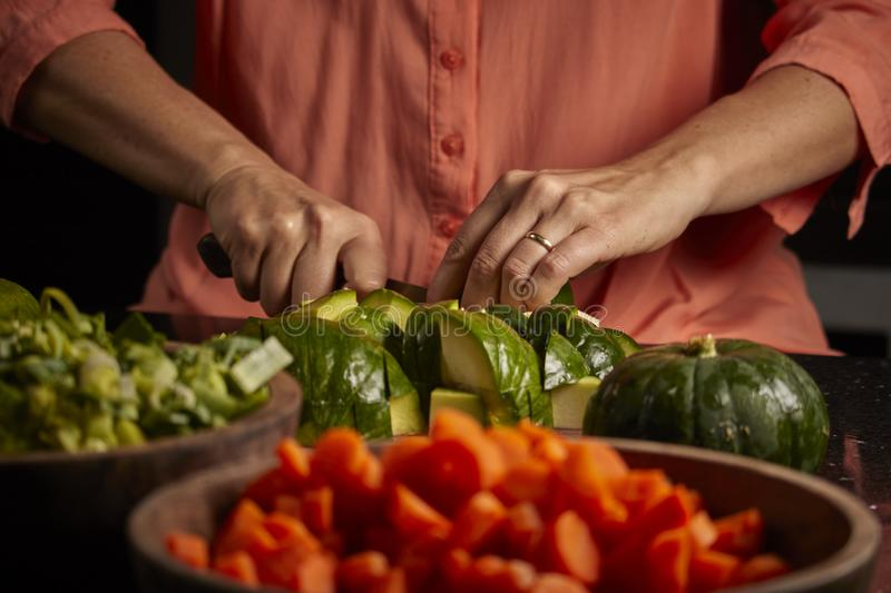 Raw vegetables of green and orange color. Kitchen. Raw vegetables of green color. Nutritious and delicious food. Woman cutting green onion, zucchini, carrots royalty free stock photos