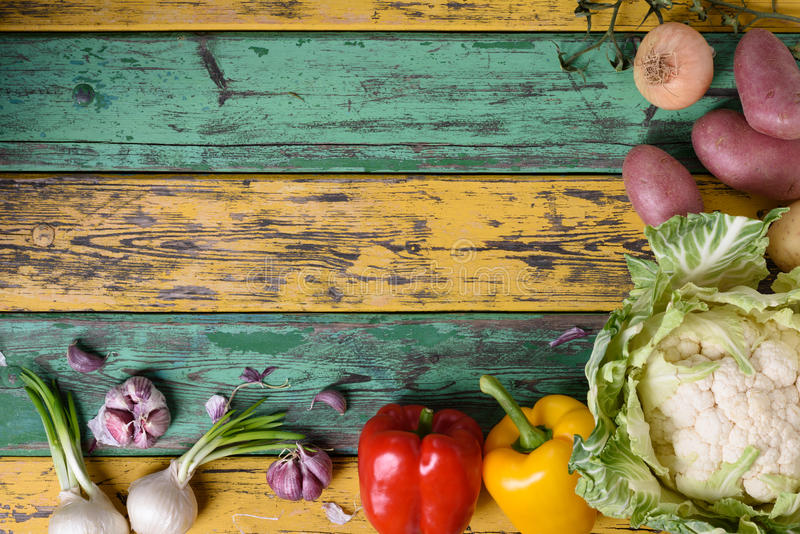 Raw vegetables. Healthy vegetarian cooking ingredients over colorful table. Organic food frame. Top view, copy space. Variety of raw vegetables. Healthy royalty free stock photo