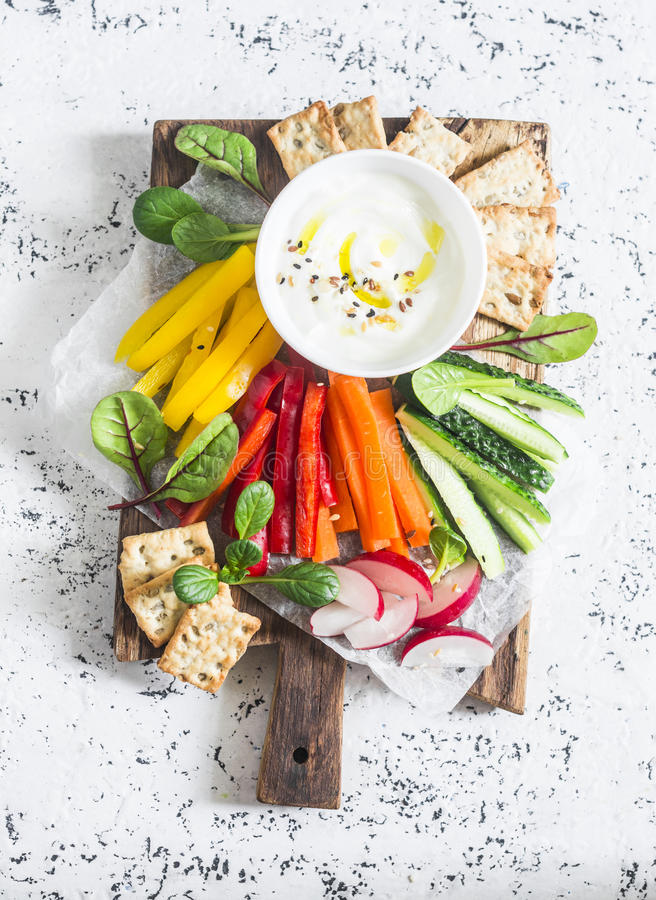 Raw vegetables and yogurt sauce on a wooden cutting board, on a light background, top view. Vegetarian healthy food stock image