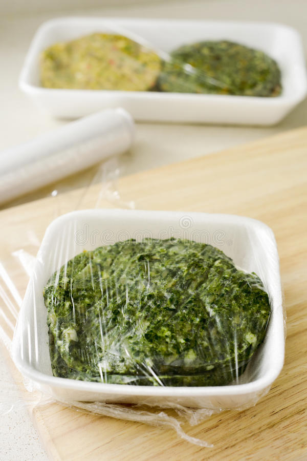Raw veggie burgers. Closeup of some different raw veggie burgers in plastic trays covered with plastic wrap ready to be introduced in the fridge or in the stock image