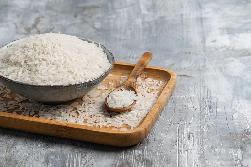 Raw white rice in ceramic bowl with wooden spoon over gray background. Wabi Sabi style. Copy space. Horizontal stock photography
