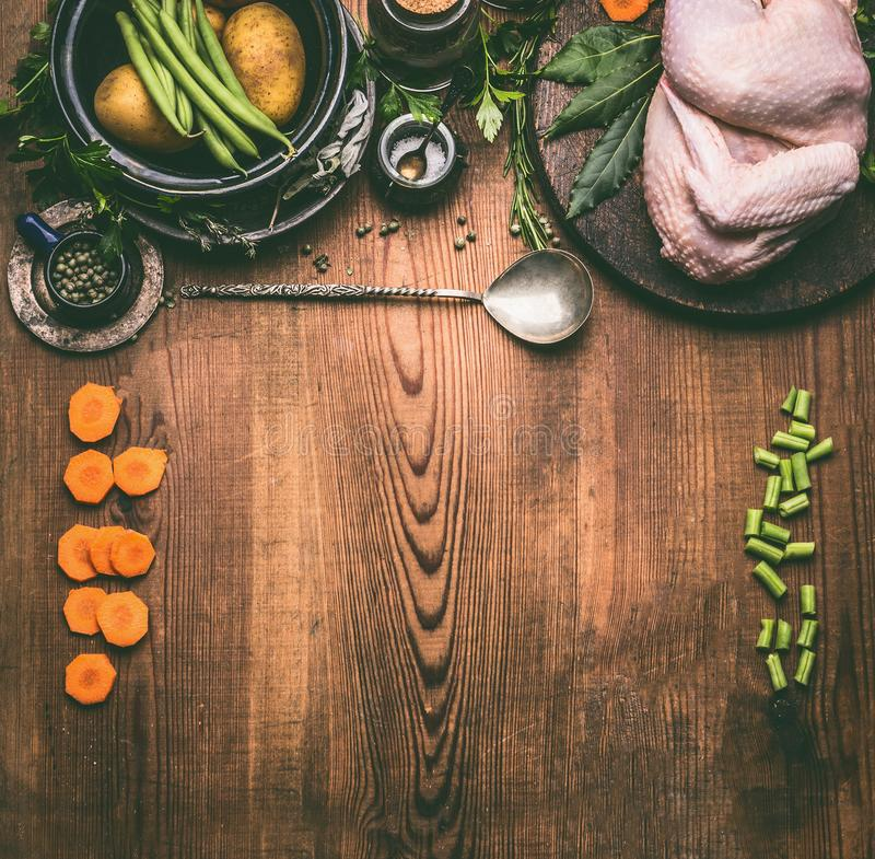 Raw whole chicken on rustic wooden kitchen table background with vegetables ingredients and spoon. Top view, frame. Chicken cooking preparation stock image