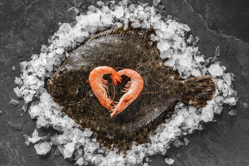 Raw whole flounder fish with shrimps stacked as a heart on ice over dark stone background. Creative layout made of fish, top view stock image