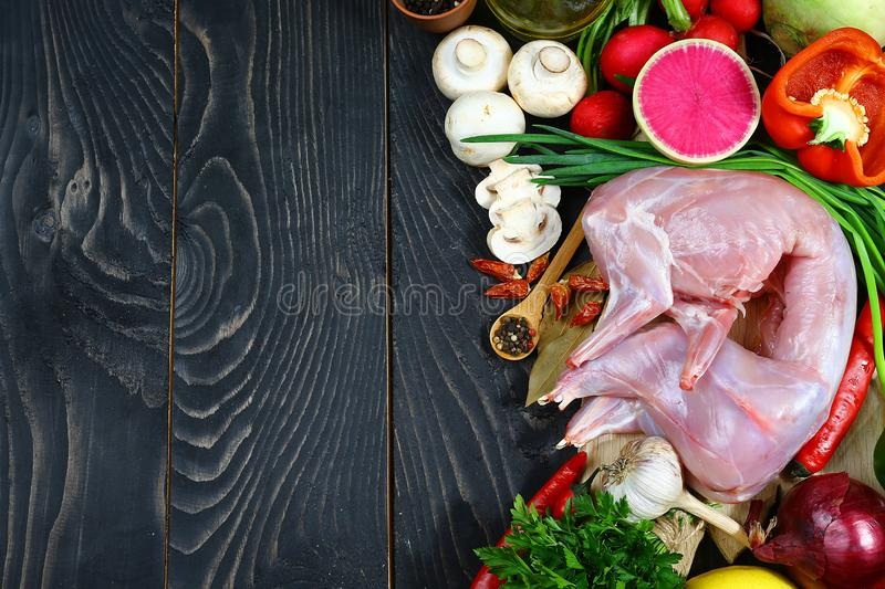 Raw whole rabbit with vegetables and spices on a dark rustic background. Top view, free space for text stock photo