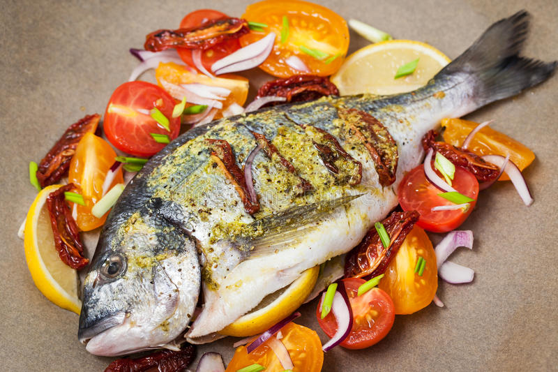 Raw whole sea bream fish and vegetables ingredients. Ready to cook royalty free stock images