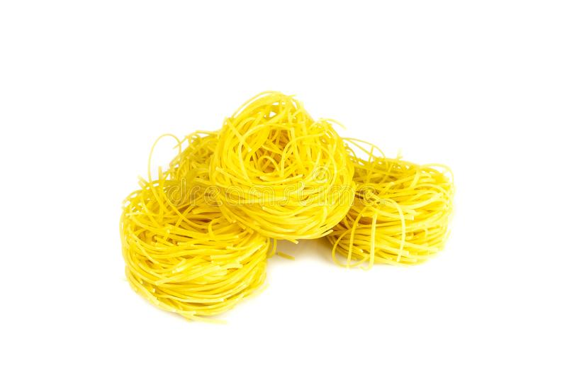 Raw yellow italian vermicelli isolated on white background. Ribbon noodles, long rolled macaroni or uncooked spaghetti stock photos
