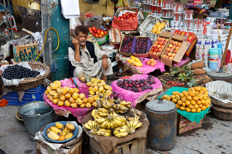 Raja Bazaar in Rawalpindi, Pakistan. RAWALPINDI, PAKISTAN - JULY 16: Unidentified Pakistani man sells fresh fruits at Raja Bazaar on July 16, 2011 in Rawalpindi royalty free stock image