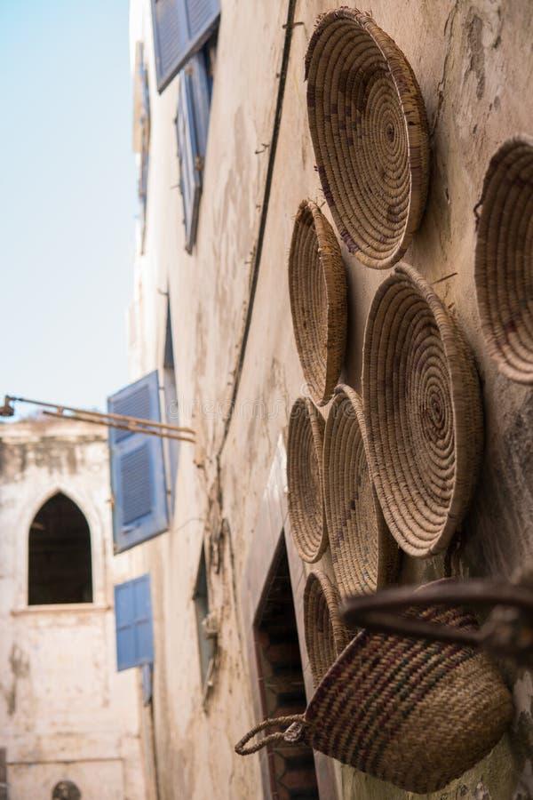 Raws de los recuerdos draided de mimbre del plato en venta que cuelgan en una pared cerca de la tienda en Essaouira, Marruecos fotografía de archivo libre de regalías
