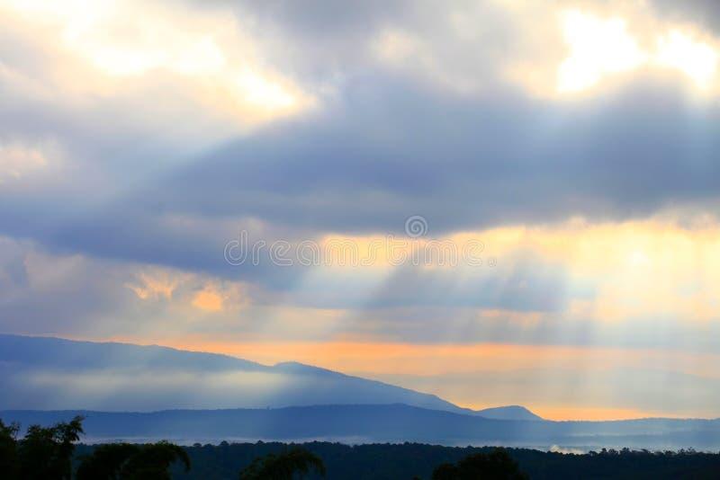 Ray av härligt solljus skiner till och med molnet över bergdalen arkivbilder