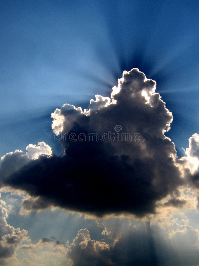 Ray Blast. A cloud beautifully disperses sunrays over the sky royalty free stock images